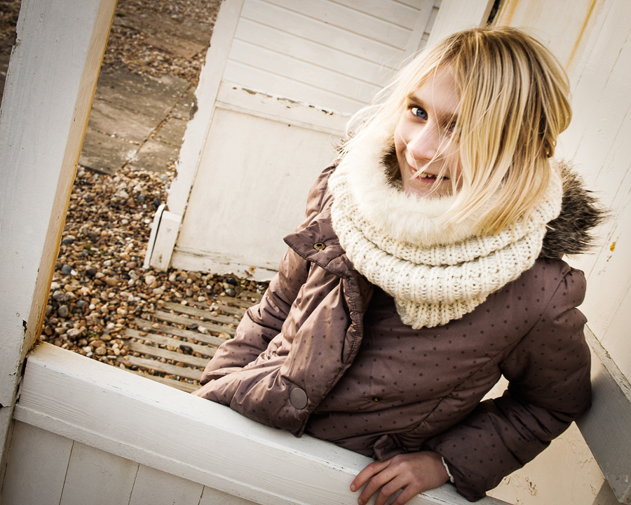 Portrait of girl by beach hut on Shoreham Beach, Shoreham-by-Sea, West Sussex.  Photo by Jenny Rutterford Photography