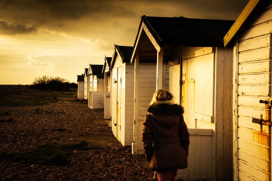 Portrait of girl walking along sunlit beach huts on Shoreham Beach, Shoreham-by-Sea, West Sussex.  Photography by Jenny Rutterford Photography