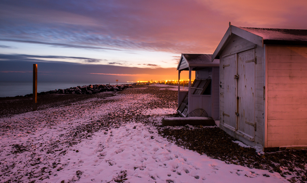 Beach huts in snow and interesting skies at dusk, Shoreham Beach, Shoreham-by-Sea, West Sussex.  Photo by Jenny Rutterford Photography