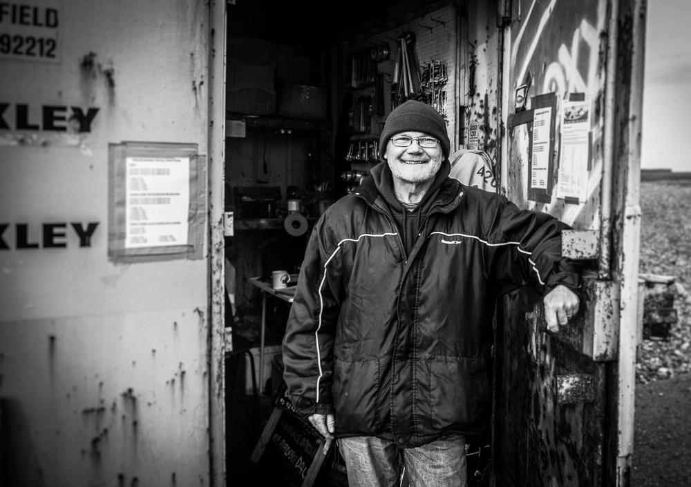 Volunteer manning the tackle hut, Shoreham-by-Sea, West Sussex.  Monochrome portrait by Jenny Rutterford Photography