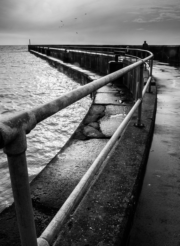 Lone fisherman on Shoreham Pier, Shoreham-by-Sea, West Sussex.  Monochrome photo by Jenny Rutterford Photography