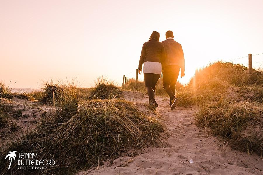 The sun sets as the couple walk along the sand dunes on Littlehampton West Beach