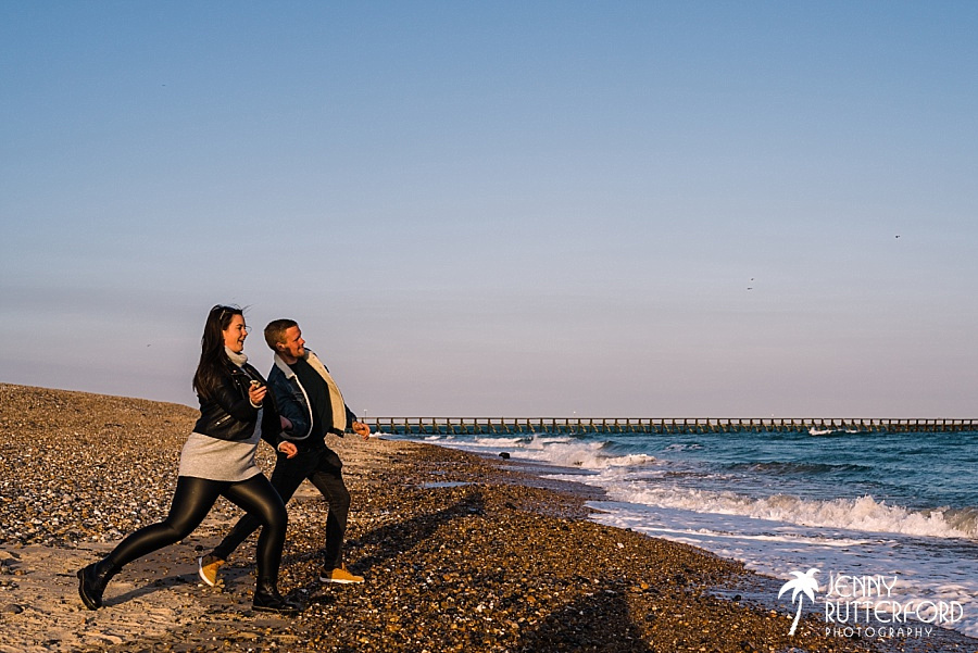 A couple practice skimming stones during their relaxed pre-wedding shoot with Jenny Rutterford Photography