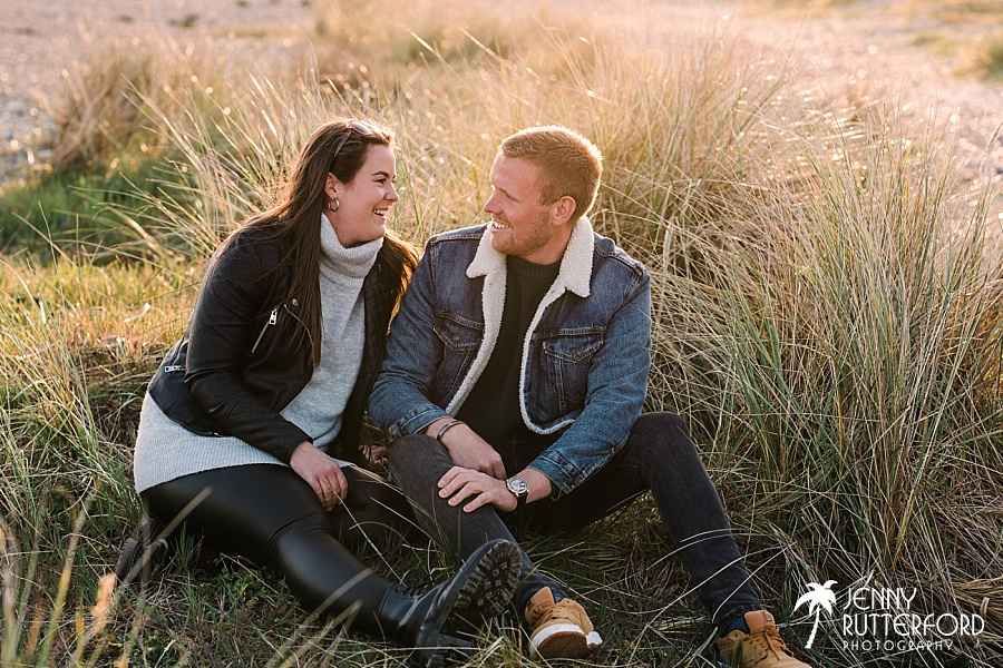Couple laughing together sitting on the sanddunes at their relaxed pre-wedding shoot