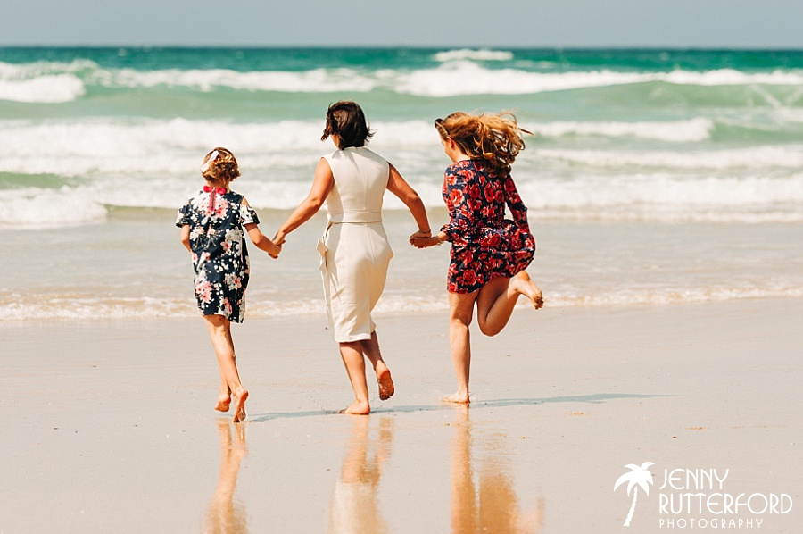 Bride running into the sea at her Lusty Glaze Beach Wedding