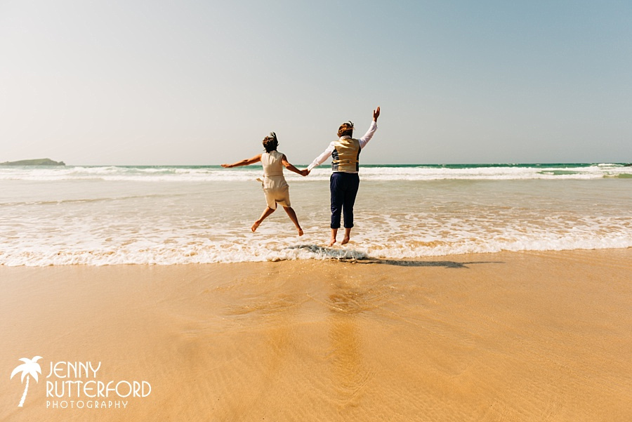Fab same sex couple jump the waves at their Lusty Glaze Beach wedding