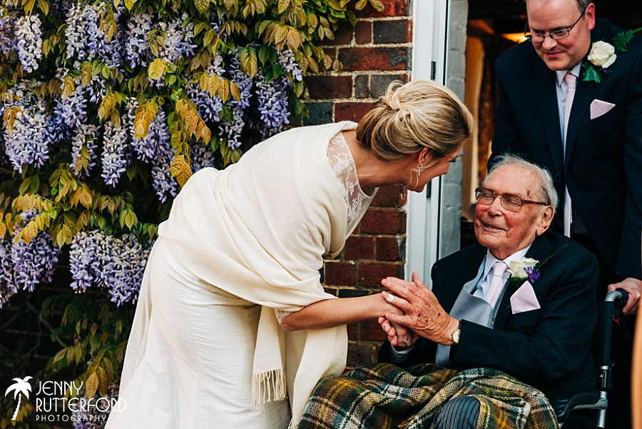 Bride greeting her father in law at her private marquee wedding