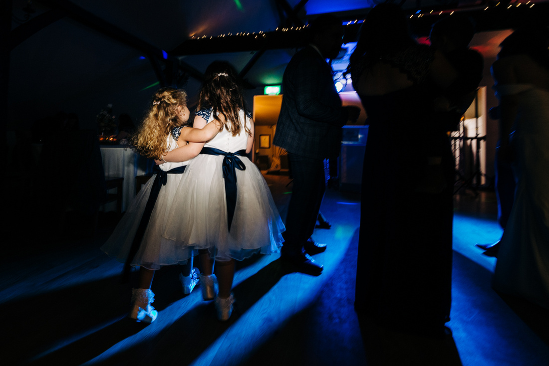 Candid photo of two flower girls and best friends at wedding, lit by gridded flash