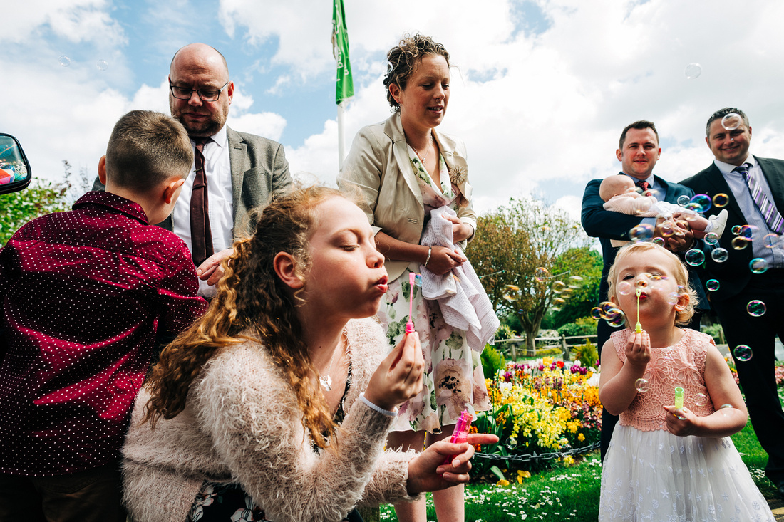 Candid photo of girls blowing bubbles after wedding in West Sussex