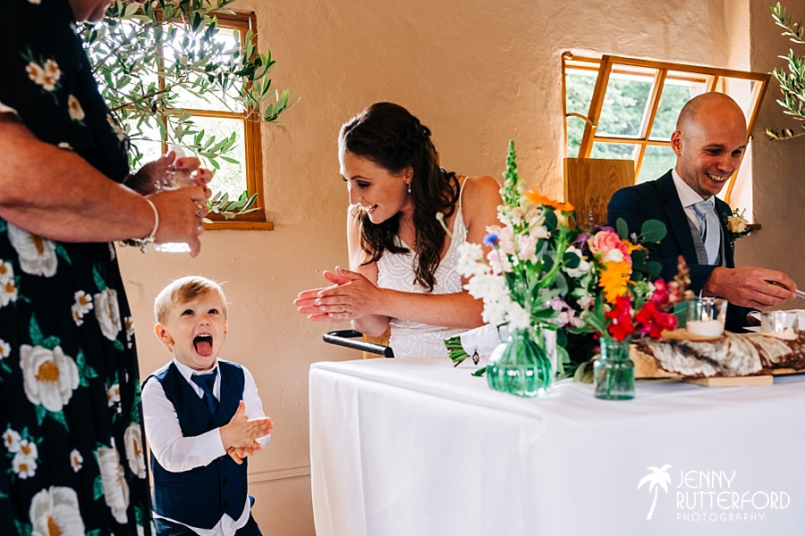 Pageboy claps as bride and groom sign register at Pangdean Barn wedding