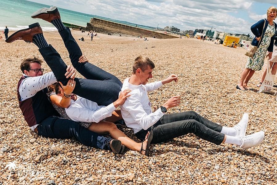 Groom's family having fun on beach at Brighton wedding