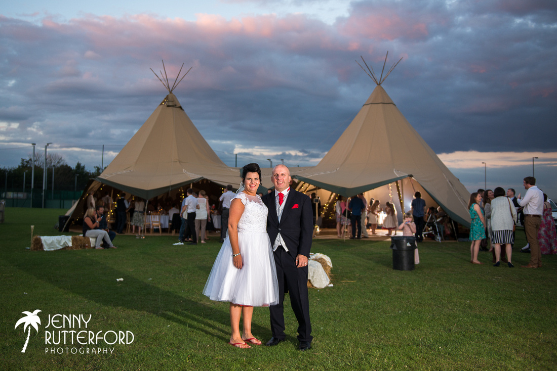 The wedding couple and dancefloor are lit by off-camera flash against a magnificent sky